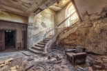 abandoned decay room with armchair and staircase